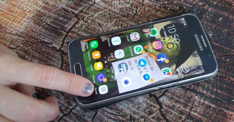 Aloitusnäyttö. Sormi osoittaa Sovellukset-nappia. Uudemmassa Android-versiossa Sovellukset tulevat näkyviin liikuttamalla sormea näytön alareunasta ylöspäin. Huawei-laitteissa Sovellukset-paikkaa ei ole ollenkaan.