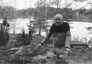 Unto Syrjä keväällä 1990 samalla kivellä kuin silloin, kun Inha kuvasi Syrjän lapset Ainon ja Unton vuosien 1916–17 tienoilla. Kuva: Maija Myllykangas.